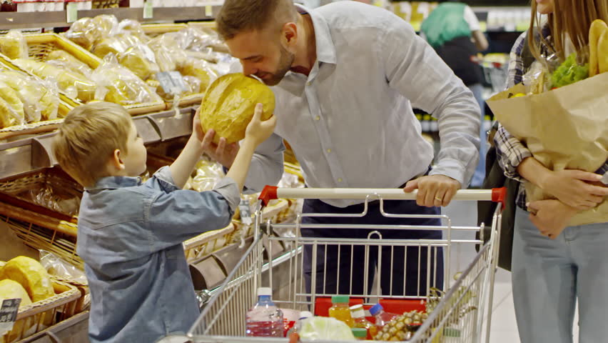 Slowmo of cute boy helping mother and father to choose bread in supermarket; man pushing shopping cart and woman carrying paper bag with groceries
