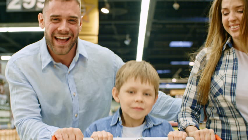 Joyous young parents running through supermarket and pushing shopping cart with little son riding it
