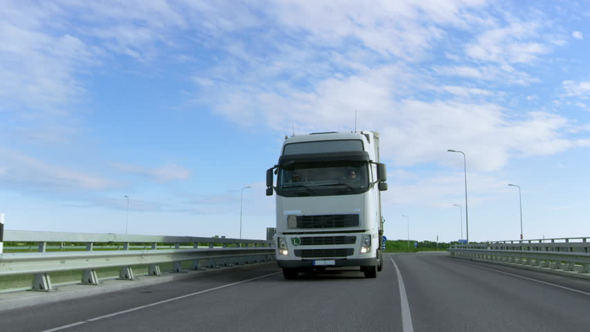 Speeding White Semi Truck with Cargo Trailer Drives on the Highway. Truck is First in the Column of Heavy Vehicles, Sun is Shining. Shot on RED EPIC-W 8K Helium Cinema Camera. #29799997