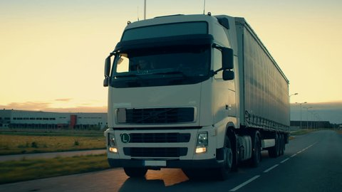 Front-View Camera Follows Semi-Truck with Cargo Trailer Driving on a Highway. He's Speeding Through Industrial Warehouse Area with Sunset in the Background. Shot on RED EPIC-W 8K Helium Cinema Camera.