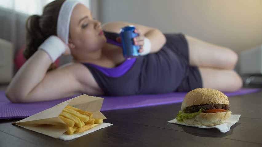 Lazy lady in sportswear lying on yoga mat eating junk food instead of training