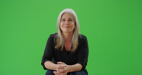Senior white woman sitting and smiling at the camera