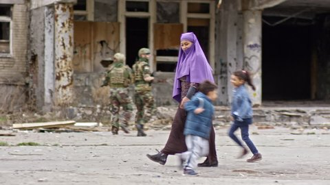 Tracking of middle-eastern woman in burqa carrying groceries and walking through street with abandoned building while her children running and playing; soldiers with firearms patrolling in background