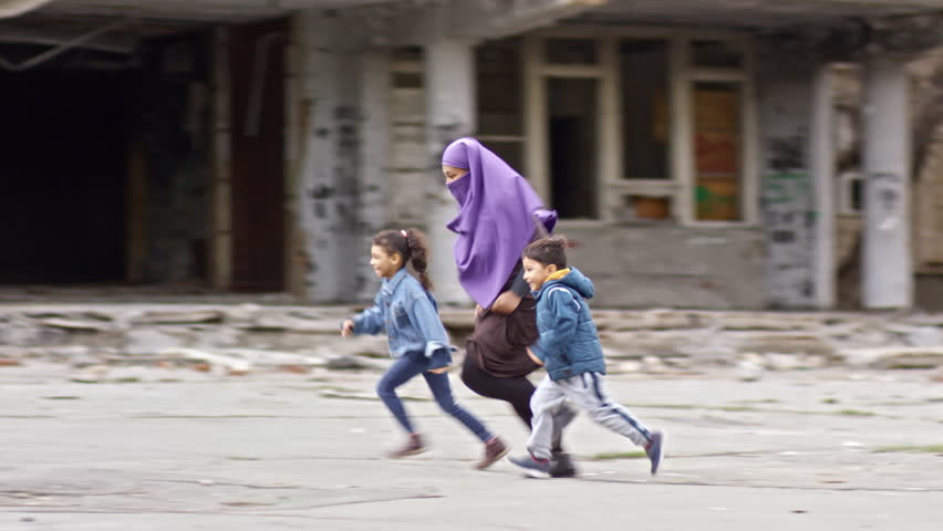 Tracking of laughing middle-eastern children and woman in purple burqa running through street with abandoned building