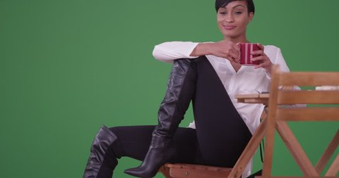 An african American woman in black boots sitting at a caf_ table drinking coffee smiles and smirks at the camera on green screen. On green screen to be keyed or composited.