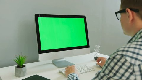 Close up shot of business man in casual shirt using computer with green screen in the modern office. Chroma key.