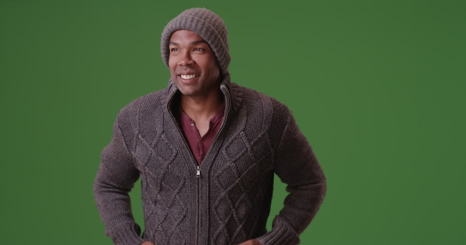 An African American man stands trembling on green screen. On green screen to be keyed or composited.