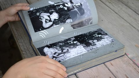 Girl leafing through a photo album with old photos which lies on the table close-up