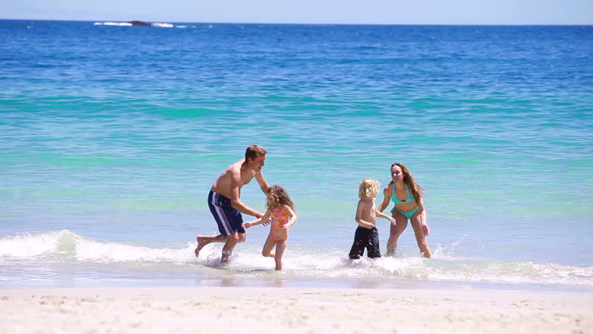 Happy family splashing each other on the beach