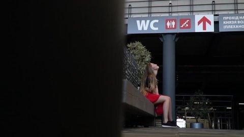 The girl is sitting on the bench and holding her breath so she does not urinate while waiting for the queue for the toilet in the mall, slow motion
