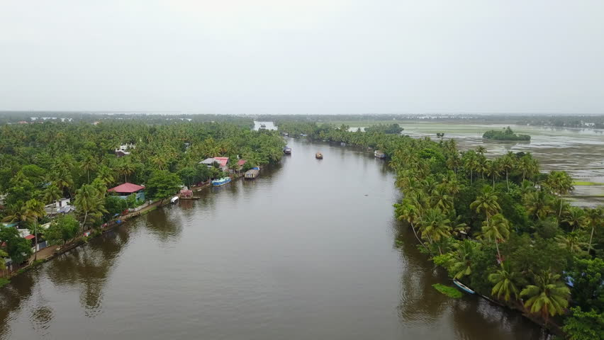 Aerial back view following a Boat Houses over the backwaters in Alleppey, Kerela with coconut trees on both sides in UHD 4K