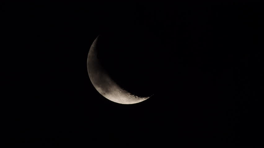 Clouds pass in front of the waning crescent moon as it moves slowly across the sky due the rotation of the earth.