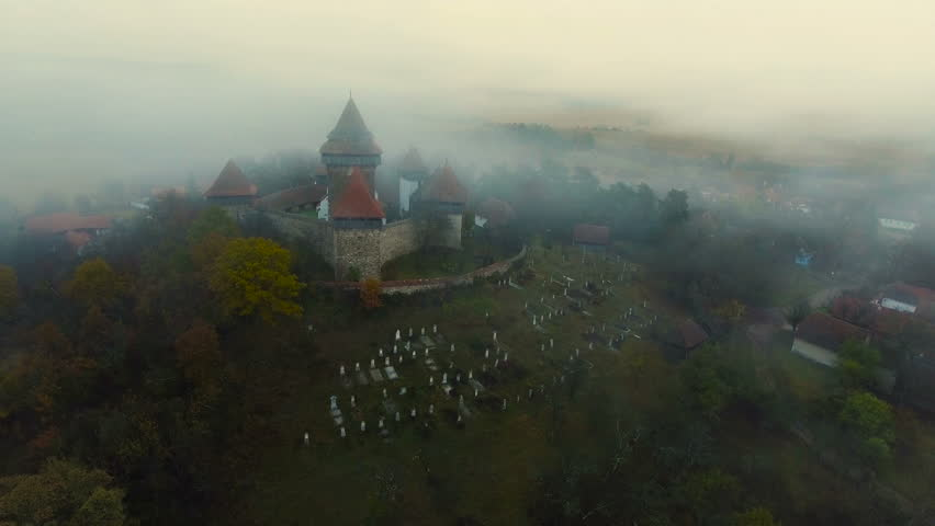 Drone flying backwards from the medieval church from Viscri village.Countryside view with Viscri fortified church in the middle surrounded by saxon houses. Transylvania, Romania. 4k footage.