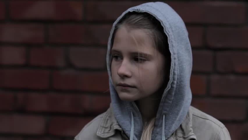 Refugee homeless child. Dark portrait of preteen girl standing in front of brick wall, she is looking unhappy and sad.