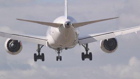 huge airplane rear view landing on runway behind landing poles lamps
