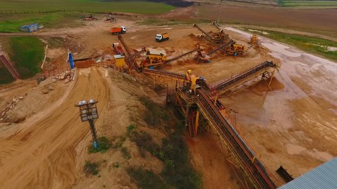 Industrial equipment at mining area. Sky view of mining equipment at sand mine. Mining conveyor working at sandpit. Aerial view of mining machinery at sand quarry
