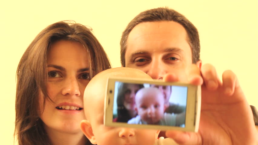 Happy young family, father, mother and child, shooting themselves with a mobile phone