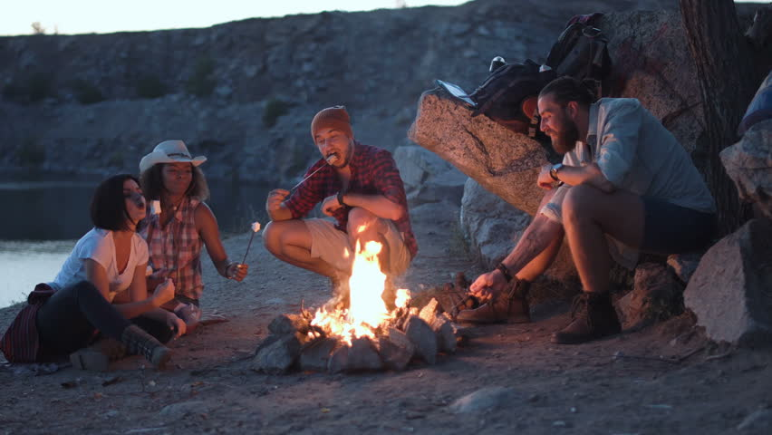 Movement stabilized 4K shot of group of multiracial people sitting around campfire grilling marshmallows and having fun on coast on lake.