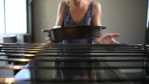 Closeup view of woman's hands taking out a baking pan from the oven. Homemade bakery