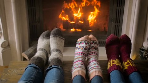 Slow motion video of feet in knitted woolen socks next to fireplace and Christmas tree
