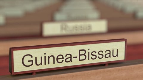 Guinea-Bissau name sign among different countries plaques at international organization. 3D rendering