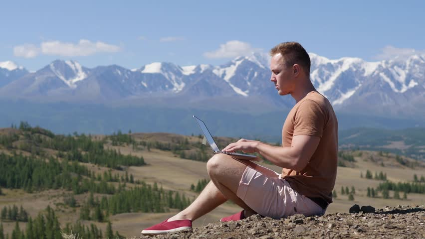 Man's hands touching a laptop of digital tablet on the background of mountains | Shutterstock HD Video #29944978