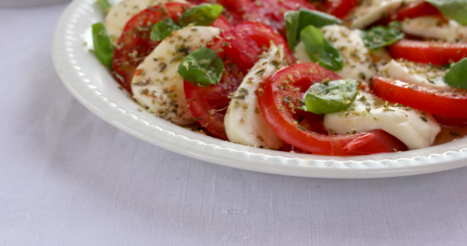 Taking a portion of Caprese salad.  Caprese salad made of sliced fresh tomatoes, mozzarella cheese and basil  served on a white plate on a table.Traditional Italian food