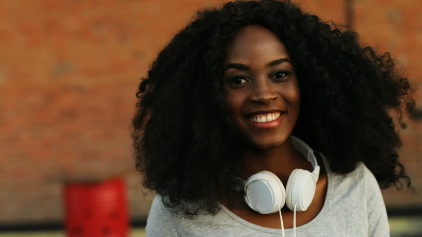 Close up shot of attractive curly hair african woman with headphone on the neck looking and smiling on the camera.