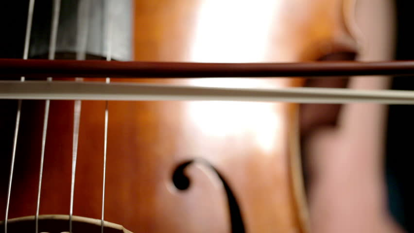 Extreme close up on the strings of a cello vibrating as the cellist pulls her bow across the strings.
