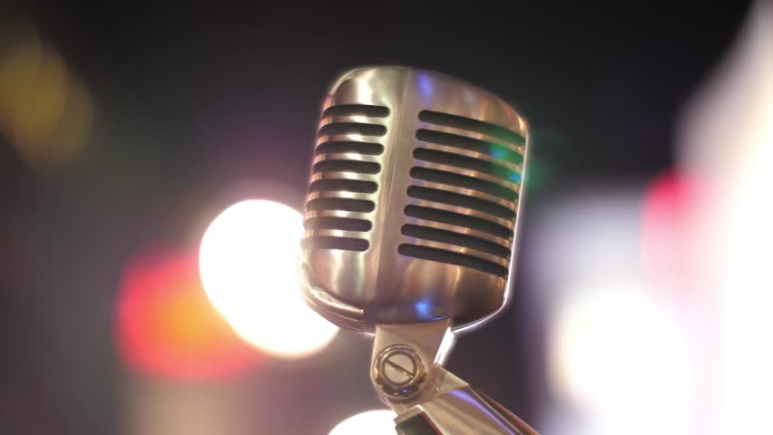 Classic retro chrome microphone over blurred bokeh circles background at night. 4K UHD.