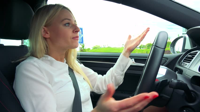 Young attractive blond woman drives a car (waits on the traffic lights) and scolds on other drivers
