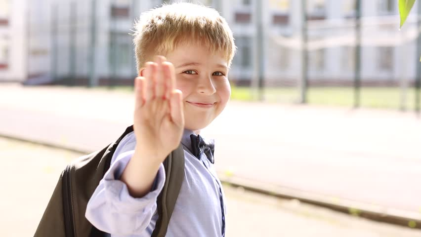 A smiling schoolboy waving good-bye and running to school.