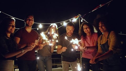 Diverse Young Party People On Rooftop Cheerful Partying With Sparkler Fire Smiling At Camera Fourth Of July Celebration Birthday Event At Night Shot on Red Epic W 8K Slow Motion