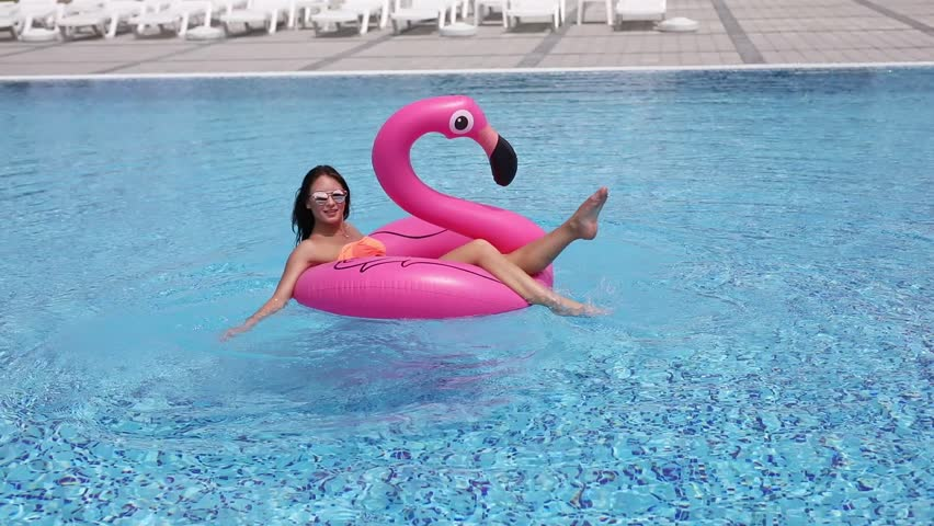 Young beautiful sexy woman in bikini swimming on inflatable pink flamingo in pool. Summer vocation