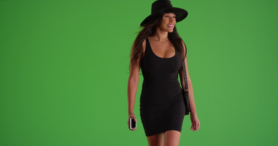 Young Latina woman in dress and hat walking toward the camera with a purse in slow motion on green screen. On green screen to be keyed or composited.