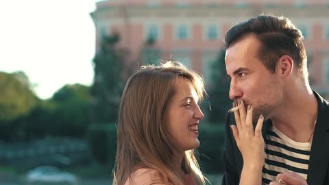 Young woman gives a cigarette to a man. Man smokes a cigarette together with a young woman. Young couple handsome man and young woman smoking cigarettes against background city buildings.