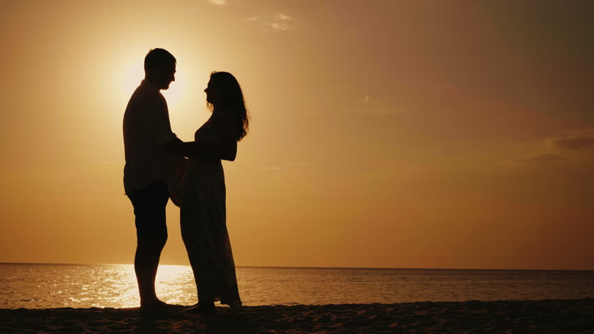 Silhouette of couple in love. They look at each other, hug and kiss at sunset. Against the background of the sea or ocean | Shutterstock HD Video #30042547