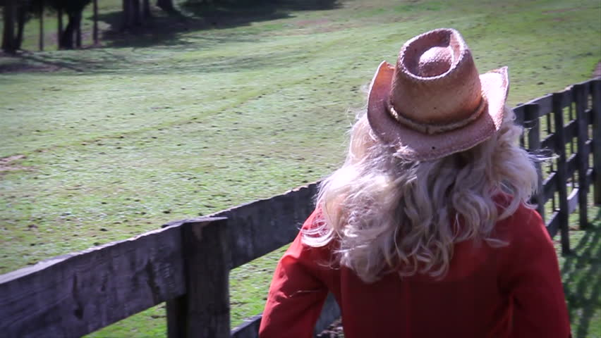 Cowgirl walking down fence line