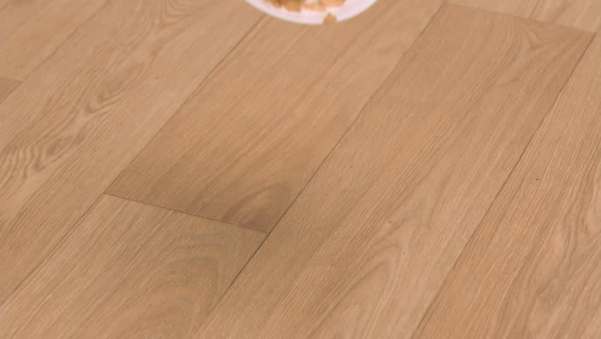 Cereals bowl falling in super slow motion on a wooden floor