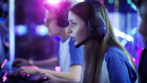Team of Professional eSport Gamers Playing in Video Games on a Cyber Games Tournament. They Talk to Each other into Microphones. Arena Looks Cool with Neon Lights. Shot on RED EPIC-W 8K.