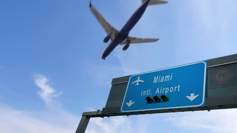 airplane flying over miami airport signboard