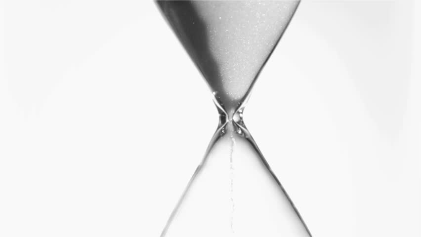 Sand flowing in super slow motion from an egg timer against a white background