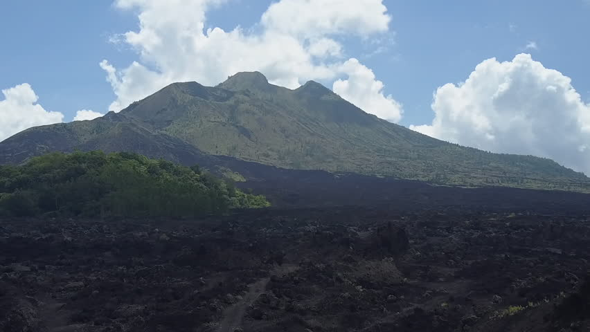 AERIAL: Flying above rough stony black lava terrain and grey ashy volcanic soil at the toot of Mount Batur towards the peak of the mountain range. Dramatic landscape at Kintamani volcano crater, Bali