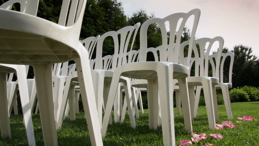 Dolly of rows of chairs at a wedding ceremony from the aisle and from the back.