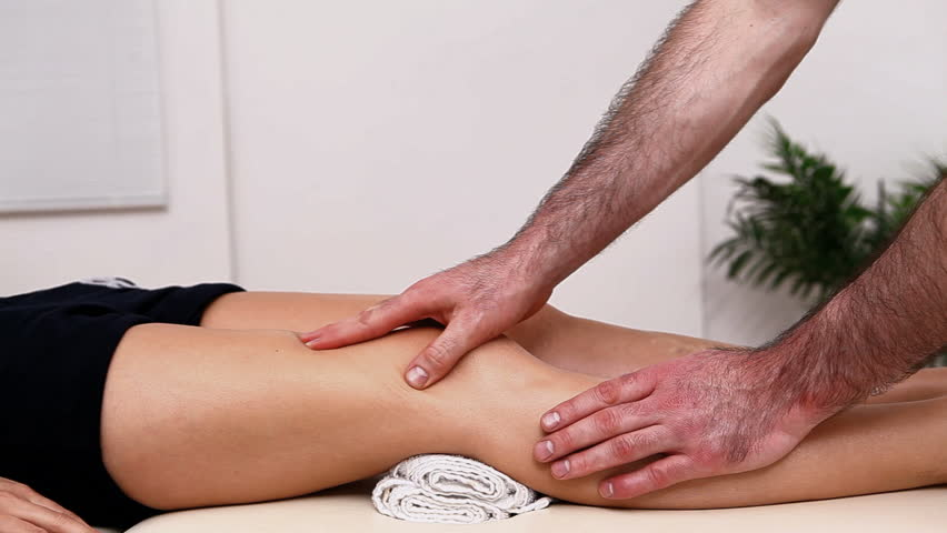 Physiotherapist massaging the thigh on a table in a therapy room