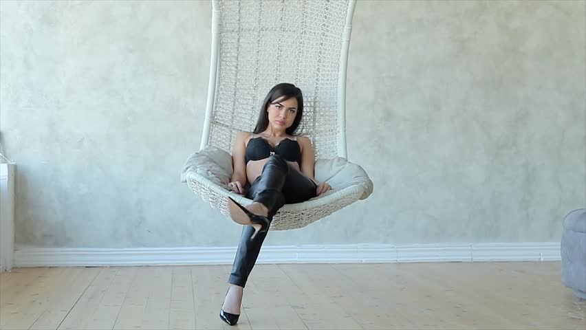 Sexy young brunette turning, sitting in the hanging chair.