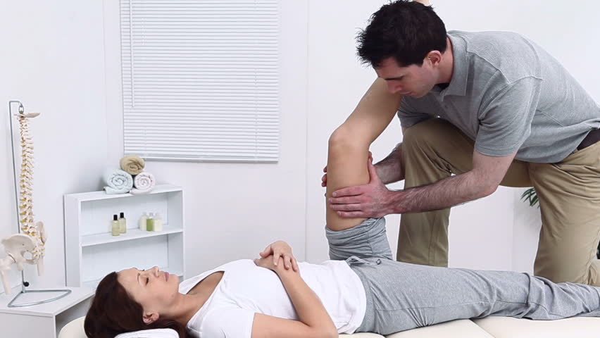 Therapist massaging the thigh of his patient in a room