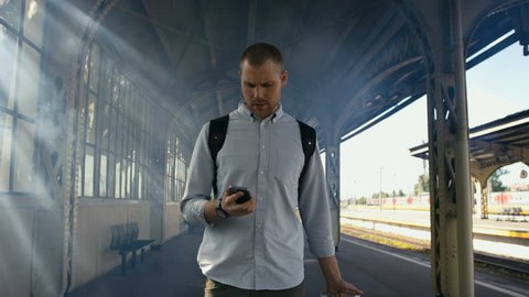 Young man walking with suitcase and looking at phone. Shot in Red Epic Dragon