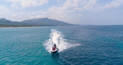 Aerial View Over Young Man Driving A Jet Ski In Ocean Clear Blue Water At Exotic Greek Island Extreme Sports Vacation Trip Adventure Exotic Summer Getaway Concept Hot Summer Day