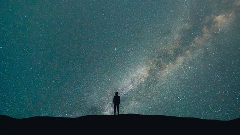 The man stand on a background of a milky way with asteroids skyfall. time lapse